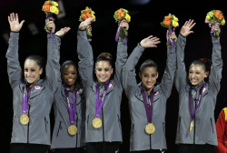U.S. gymnasts, left to right, Jordyn Wieber, Gabrielle Douglas, McKayla Maroney, Alexandra Raisman, Kyla Ross raise their hands on the podium during the medal ceremony during the Artistic Gymnastic wo