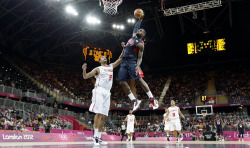 USA's Lebron James, right, dunks over Tunisia's Mohamed Hadidane, left, during the first half of a preliminary men's basketball game at the 2012 Summer Olympics