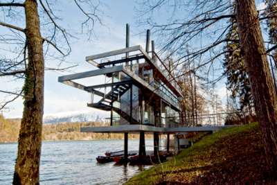 evolomagazine:  Rowing Center Takes Subtle Eye Towards Landscape The Bled Rowing Center in Bled, Slovenia, designed by architects Sandra Banfi Škrbec, Iztok Lemajič, Miha Kajzelj and Iztok Kavčič, seeks to render as minimal an impact on the landscape as possible. Using the camouflaged set of structural interventions and treatments of exterior walls, the structure is able to float above the wooded landscape, appearing only as a collection of horizontal lines amid a cluster of irregular tree trunks.
