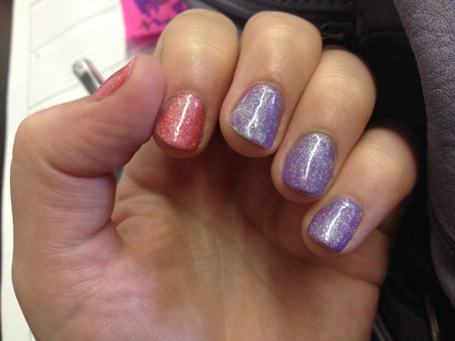 "At work, admiring my purple and pink holo pistol manicure! The purple is Rimmel's ""Wild Orchid"". I am so in love with this color at the moment that I kind of try and sneak it in when I can. The Pink is LA Colors in ""Electric Charge"" Then I put Milani 3D Holographic in ""509 HD"" on top. It is a pretty silvery holographic rainbow-y glitter-gasm. Mhmm.  Note the chipping/tip wear. This is a few days in."