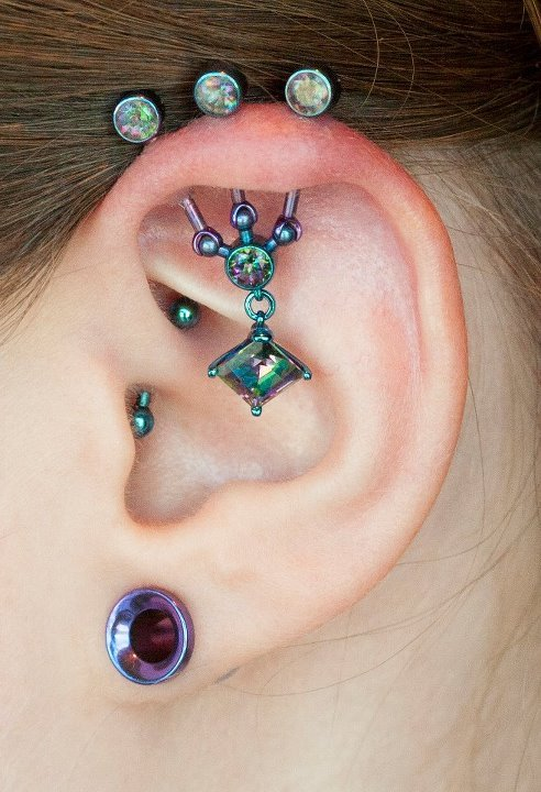 Healed Multi-point Industrial by Bryan featuring mystic topaz gems set in titanium. Anodized in-house at [Born This Way Body Arts - Knoxville, TN]