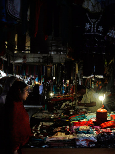 Kashmiri women purchase clothes at a local market in Srinagar, India on Aug. 1. Factories and workshops across India were up and running again Wednesday, a day after a major system collapse led to a second day of power outages and the worst blackout in history leaving an estimated 620 million people without electricity. (Mukhtar Khan/Associated Press)