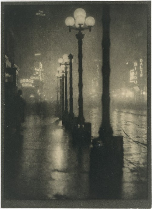 "Broadway at Night, by Alvin Langdon Coburn ca. 1910 [from last year's Metropolitan Museum of Art exhibit, Night Vision: Photography After Dark] ""It is only at twilight that the city reveals itself to me in the fulness [sic] of its beauty, when the arc lights on the Avenue click into being. Many an evening I have watched them and studied carefully just which ones appeared first and why. They begin somewhere about Twenty-sixth street, where it is darkest, and then gradually the great white globes glow one by one, up past the Waldorf and the new Library, like the stringing of pearls, until they burst out into a diamond pendant at the group of hotels at Fifty-ninth street. Probably there is a man at a switchboard somewhere, but the effect is like destiny, and regularly each night, like the stars, we have this lighting up of the Avenue."""