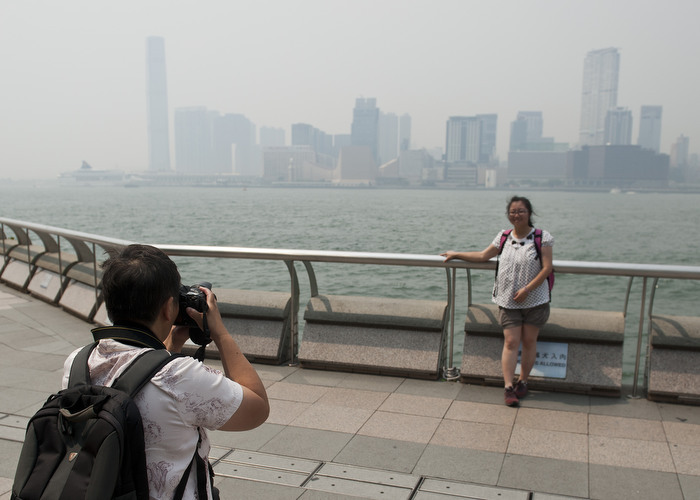 "HONG KONG: Aug. 2, 2012 — A tourist takes a photo with the hazy skyline of Kowloon in Hong Kong Thursday, Aug. 2, 2012. The air pollution index at 164 API in Causeway Bay roadside, ranked as ""very high"" on the Air Pollution Index. Hong Kong Observatory predicts the air pollution is due to the air masses Typhoon Saola and Typhoon Damrey are near Hong Kong and bringing a very hot weather with minimal wind. (Photo by JUSTIN CHIN)"