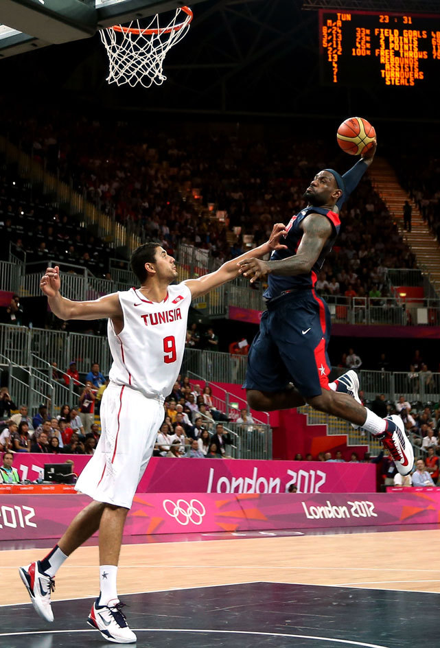 LeBron James dunks over Mohamed Hadidane during Tuesday's game between the United States and Tunisia. Team USA led by just 13 points at halftime before responding with a 21-3 scoring blitz on the way to a 110-63 victory. (Ezra Shaw/Getty Images)  THOMSEN: Great Britain using Olympics to grow basketballGALLERY: Players to Watch in London | Rare LeBron James Pics