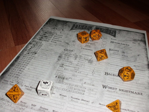 Aaron has bought himself some Deadlands dice (despite his constant piss taking of official dice sets when they appeared in the New Releases) so he's taken an action shot of dice and character sheet. NERD.