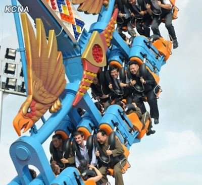 North Korean leader Kim Jong-un enjoys a roller coaster ride at the Rungna People's Pleasure Ground in Pyongyang. British diplomat Barnaby Jones, middle of front row, went along for the ride.