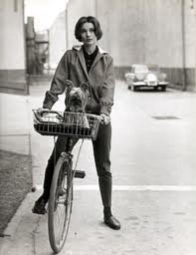 AUDREY HEPBURN RIDING HER BIKE BETWEEN SCENES DURING THE FILMING OF SABRINA.