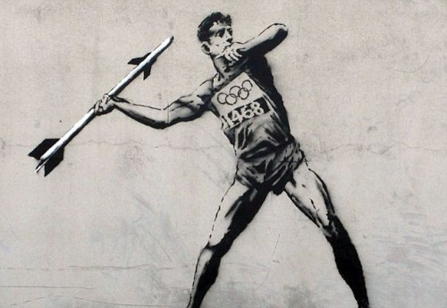 This is exactly what it looks like - a bloke throwing a javelin, but instead of a javelin it's a missile. What's funny is that there is actually a kind of missle called a javelin… however this isn't one. This is a commentary on the fact that the British government has put missiles on tower blocks in East London.  However… it's also got a deeper meaning. Can you guess what it is?
