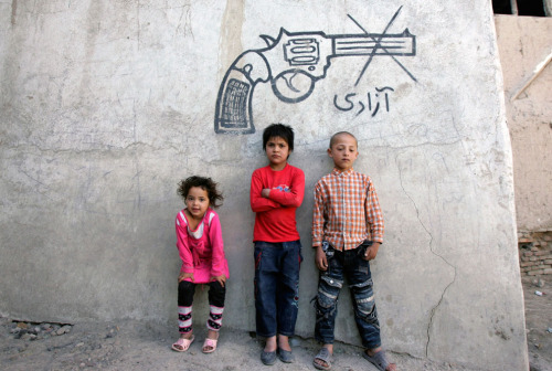 """Afghan children pose for a photograph beneath graffiti, with writing that reads, 'freedom' in Kabul, on June 22, 2012."" (AP Photo/Ahmad Nazar)"