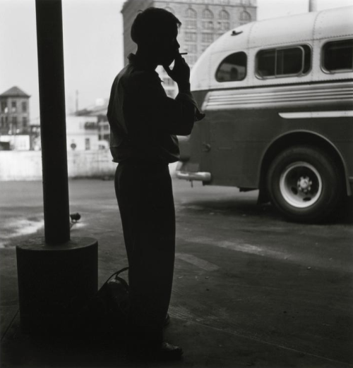 Man takes a cigarette break at a bus terminal in downtown Pittsburgh. The Pennsylvania Railroad's Union Station is pictured in the background, 1950 Elliott Erwitt