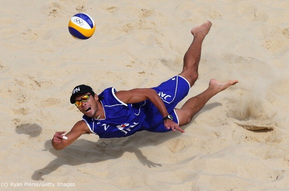 Katsuhiro Shiratori of JPN dives for a shot during the Men's Beach Volleyball preliminary match