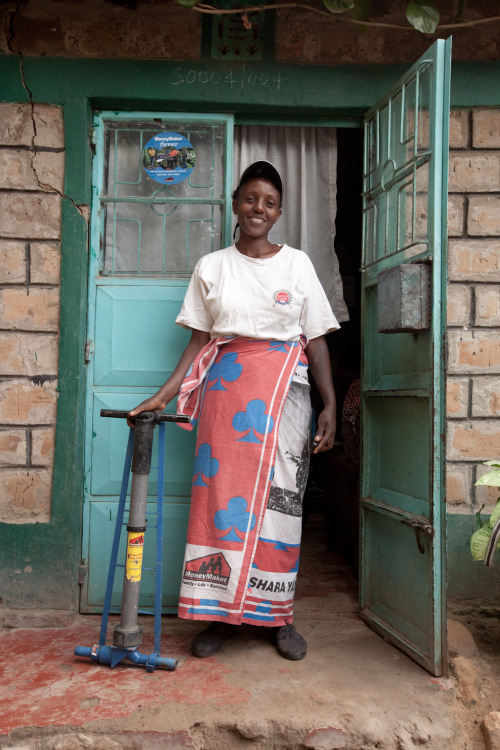 Penniah, a farmer and mother, stands proudly in front of her home in Kenya where she raises her three children. In her hand is an irrigation pump for farming, which allows her to increase her crop yield and therefore her income. Learn more at www.theadventureproject.org.
