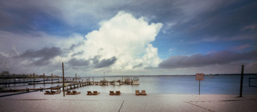 Pinhole: Intercoastal on Flickr.Zero Image 69, f235, Kodak Portra 160, about 2 seconds Shot during a one-day roadtrip to Florida. This is the intercoastal waterway in Navarre, where we had breakfast and bloody Marys after our long drive down.  The islands along this stretch of the coast serve as barriers to the mainland. Most are tiny spits of sand less than a half mile wide. They're beautiful, with the ocean on one side and the intercoastal on the other, so people want to build tall, obnoxious buildings. It leads to overdevelopment, but it's not smart development because the islands aren't good for building on. Squalls and hurricanes add and subtract land from these spits of sand, so the islands are forever shifting around (like they're supposed to do). Over time, only man-made interventions will prevent man-made condo towers from toppling into the sea. All that…doesn't stop me from dreaming about owning one of these obnoxious houses. I feel like such a hypocrite at times.