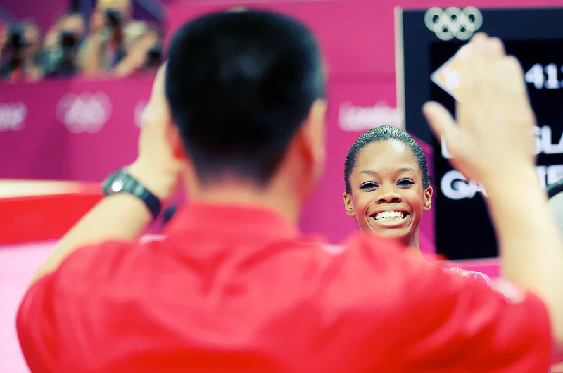 OLYMPICS DAY 6 Gabby Douglas smiles as she looks at coach Liang Chow after the balance bar in Gymnastics Women's Individual All-Around Photo by Streeter Lecka