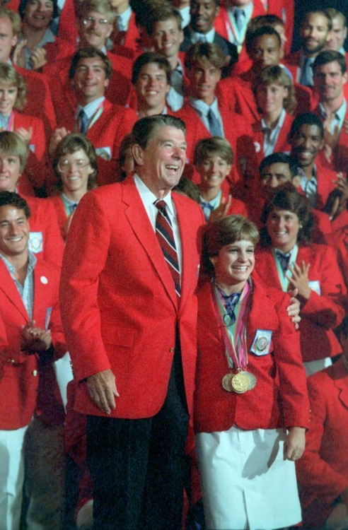 "On this day in 1984, Mary Lou Retton wins gold Before Gabby Douglas, there was Mary Lou.  Here, the first American woman to win the Olympic gold medal in the all-around gymnastics competition stands shoulder-to-head with President Ronald Reagan. Between Mary Lou Retton and Gabrielle ""the Flying Squirrel"" Douglas, there have been only two other American all-around champions; Douglas is the first to come home with both this and the team gold. Photo from the Reagan Library: President Reagan posing with Mary Lou Retton and the 1984 U.S. Olympic team at the Century Plaza Hotel, Los Angeles, California. 8/13/84."