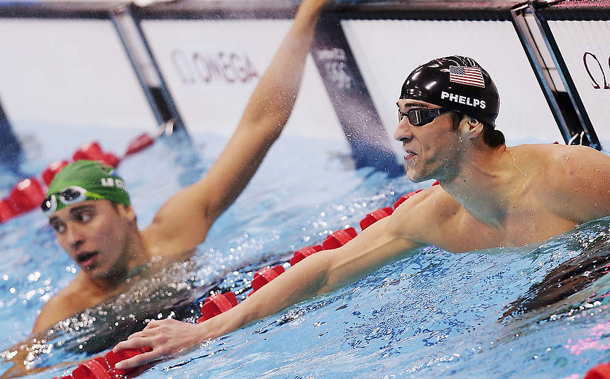Michael Phelps of the U.S. spits out water next to South Africa's Chad le Clos (L) after winning gold in the men's 100m butterfly final during the London 2012 Olympic Games at the Aquatics Centre August 3, 2012. Le Clos won the silver. REUTERS/Tim Wimborne