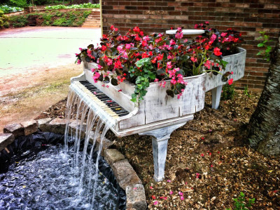 Waterfall Piano built and designed by Bill Metzgar 1885 Steinway with bad termite damage to the inner structure beyond repair, turned into a fountain by Bill Metzgar for his mom's  mother's day. It has a 2000 gallon per hour pump in the pond and a flex hose from the pump up into the piano where he used a construction of PVC to distribute the water across the keys which are sealed with fiberglass resin. Designer can be reached at b.metzgar@live.com.