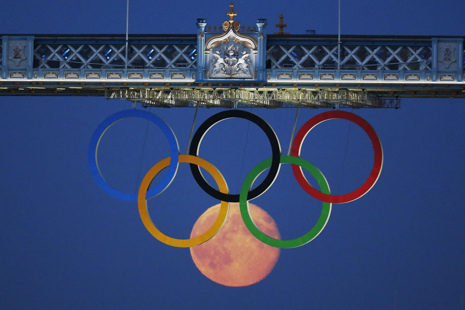 The full moon rises through the Olympic Rings, hanging beneath Tower Bridge, during the London 2012 Olympic Games - August 3, 2012.