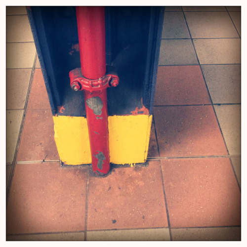 Red pipe on the blue post with yellow base.