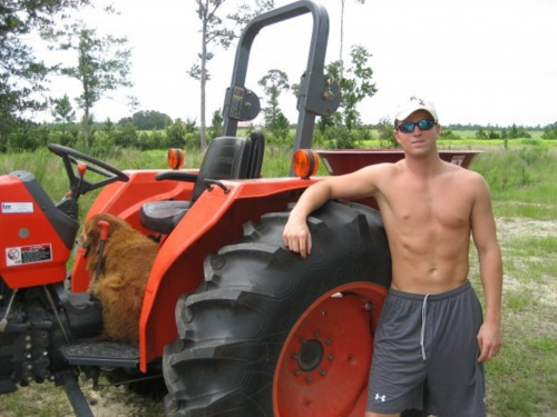 Shirtless redneck farm boy, beside his tractor.