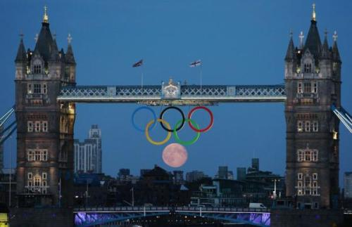 olympics:  Full moon rises through the Olympic rings at Tower Bridge in London. (c) Reuters/Luke MacGregor