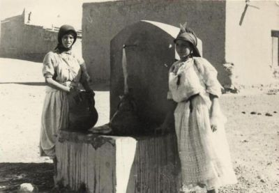 Two Ist-Hediddou women fetching water in Imilchil, Morocco. September 1967. M. Peyon.