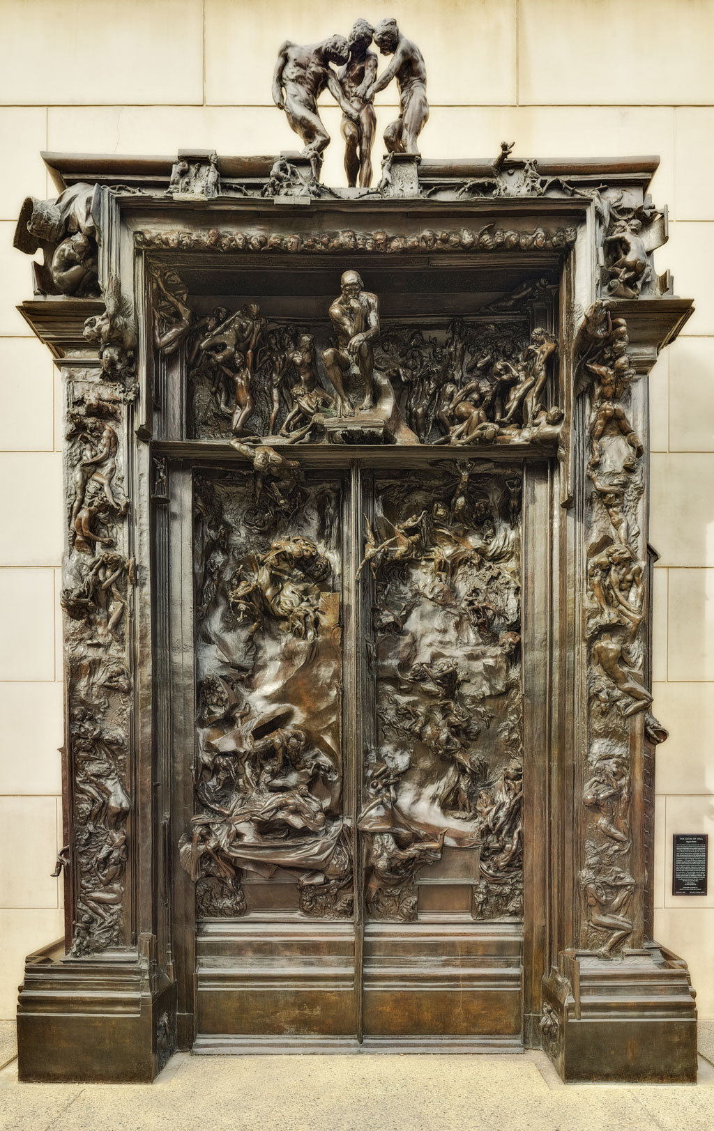 "The Gates of Hell (La Porte de l'Enfer) - Auguste Rodin: depicts a scene from ""The Inferno"", the first section of Dante Alighieri's Divine Comedy. It contains 180 figures. The figures range from 15 cm high up to more than one metre. Several of the figures were also cast independently by Rodin: The Thinker (Le Penseur), also called The Poet, is located above the door panels. One interpretation suggests that it might represent Dante looking down to the characters in the Inferno. Another interpretation is that the Thinker is Rodin himself meditating about his composition. Others believe that the figure may be Adam, contemplating the destruction brought upon mankind because of his sin. The Kiss (Le Baiser) Rodin wanted to represent their initial joy as well as their final damnation. Ugolino and His Children (Ugolin et ses enfants) depicts Ugolino della Gherardesca, who according to the story, ate the corpses of his children after they died by starvation. (Dante, Inferno, Canto XXXIII) The Three Shades (Les trois Ombres) The figures originally pointed to the phrase ""Lasciate ogne speranza, voi ch'intrate"" (""Abandon all hope, ye who enter here"") from Canto 3 of the Inferno. Paolo and Francesca is shown on the left door pane. Paolo tries to reach Francesca, who seems to slip away. Adam and Eve. Rodin asked the directorate for additional funds for the independent sculptures of Adam and Eve that were meant to frame The Gates of Hell. However, Rodin found he could not get Eve's figure right. Consequently, several figures of Eve were made, none of which were used, and all of them were later sold."