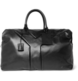 Hamptons Large Leather Holdall Bag by Yves Saint Laurent Take the stylish route to weekends away by packing up this Yves Saint Laurent leather holdall. The understated accessory is detailed with a subtle 'Y' emblem on each side, and is crafted from tactile leather giving it a slick finish.