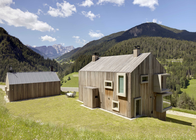 Casa Prè de Sura is a minimalist home located in Italy, designed by Austrian-based architects Casati. The exterior is delineated by vertical wooden planks that outline extruding windows. The windows are scattered throughout the facade, and the master bedroom window wraps around two walls.