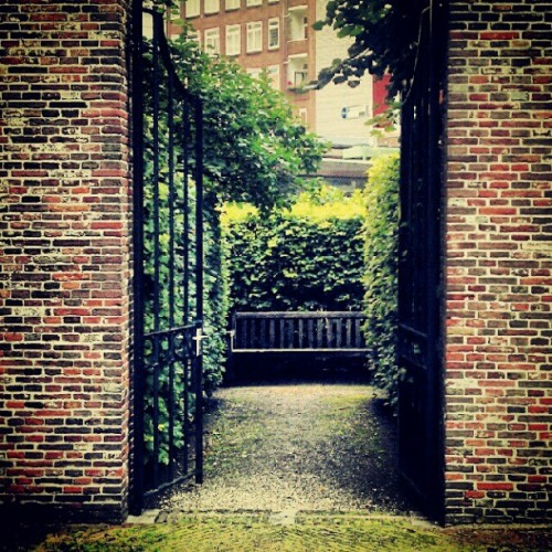 CONSTANT CONVERSATIONS #gate #wall #journey #garden #bricks #path #way #invitingroad #cloud #sky #view #travel #nature #bench #summer #rain #beautiful #branches #tree (Taken with Instagram)