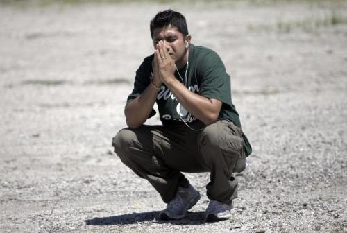 A family member prays in a parking lot while waiting to hear information about his loved ones inside the Sikh Temple on S. Howell Avenue where a shooting occurred, Sunday.  At least 7 dead, including shooter, at Sikh Temple via the Milwaukee Journal Sentinel