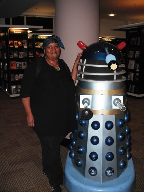 fatpeopleofcolor:  A fat black, British woman standing beside a Dalek. Woman wears black jeans, a black shirt and a blue headscarf. The whole Dr Who and Torchwood universe is loved by many bisexual people, and I'm no exception. I saw the Dalek after leaving a meeting of a Christian Kink group which was being held in a bookshop in central London.  The acceptance I've found of various genders, races, faiths and sexualities in both the fictional and real world is something that gives me hope.  It isn't always depressing to be so different.