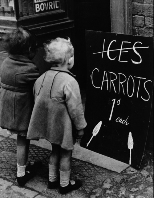 cruello:  Two little girls read a board advertising carrots instead of ice lollies. Wartime shortages of chocolate and ice cream made such substitutions a necessity, April 1941. Photo: Fox Photos/Getty Images via