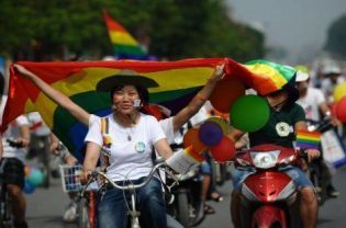"Vietnam Holds First Gay Pride Parade  The first gay pride parade in communist Vietnam took place in the capital Hanoi on Sunday with dozens of cyclists displaying balloons and rainbow flags streaming through the city's streets. Organised by the city's small but growing Lesbian Gay Bisexual and Transgender (LGBT) community, the event went ahead peacefully with no attempt by police to stop the colorful convoy of about 100 activists despite their lack of official permission. ""There was no intervention which is a good thing for Vietnam,"" said one of the organizers, Tam Nguyen. She said the parade had helped unite the LGBT community and raise awareness among ""curious"" onlookers, although many had no idea what the rainbow flag — an international symbol for LGBT groups — symbolized. The cyclists attracted no hostility — and only a little attention — as they made their way down Hanoi's busy streets."