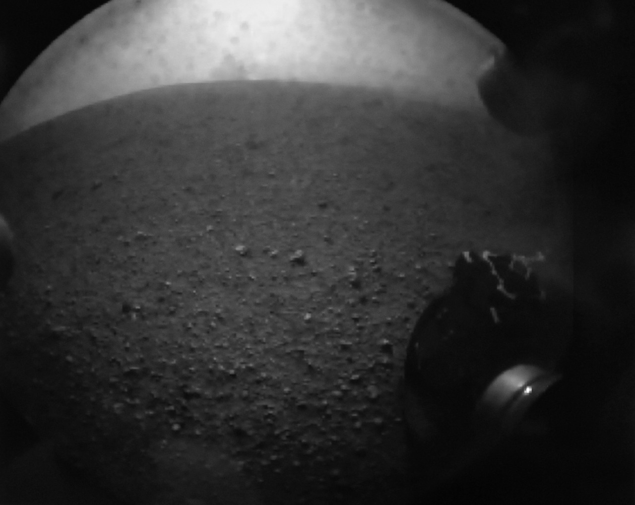 In this image from NASA TV, shot off a video screen, one of the first images from the Curiosity rover is pictured of its wheel after it successfully landed on Mars.  The video screen was inside the Mars Science Laboratory (MSL) team inside the Spaceflight Operations Facility for NASA's Mars Science Laboratory Curiosity rover at Jet Propulsion Laboratory in Pasadena, California August 5, 2012. The Curiosity rover landed successfully landed on the surface of Mars. [REUTERS/Courtesy NASA TV/Handout]