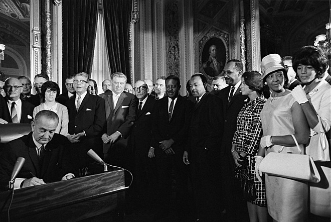 ourpresidents:  On August 6, 1965, The Voting Rights Act was signed by President Lyndon B. Johnson.  The Act applied a nationwide prohibition of the denial or abridgment of the right to vote on account of race or color.  It outlawed discriminatory literacy tests, expanded voting rights for non-English speaking Americans, and appointed Federal examiners to oversee voter registration and elections. Read More The law had an immediate impact. By the end of 1965, a quarter of a million new African American voters had been registered, one-third by Federal examiners.  In this photo, LBJ signs the Voting Rights Act in the Capitol Rotunda, Washington, DC.  Martin Luther King, Jr. and other civil rights leaders stand behind him. LBJ's speech from the signing here