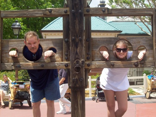 Allie and her dad in the stocks at Magic Kingdom during her wish trip to Disney World.