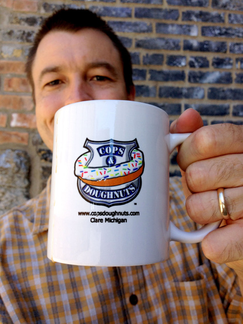 "Mugshot Monday - ""Cops & Doughnuts"" coffee mug with Birchwood Blend by Peace Coffee My cousin Eileen and her husband Brent sent me this coffee mug after visiting Clare, Michigan recently. There's a cool story behind it, which Brent summarized:  The back story is that the bakery was going out of business, so these cops — I think there are nine of them — all chipped in and bought the store. They re-branded it to the logo/name on your mug and saved the bakery. Their Bacon Maple Long John was AWESOME!  It's a brilliant move by these police officers to not only ""take back"" the cliché image of cops eating doughnuts — they actually OWN that image now! Thanks to Brent and Eileen for the cool coffee mug and the Cops & Doughnuts coffee beans (not pictured)! I need to stop by for a doughnut there some day."