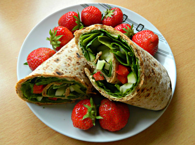 seedsnsmiles:  Lunch - wholewheat wrap filled with original hummus, baby spinach, red bell pepper, courgette, black pepper and sunflower seeds with strawberries.