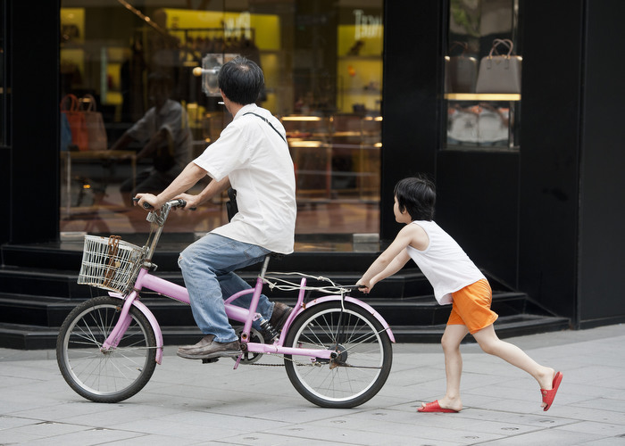 HONG KONG: Aug. 5, 2012 — A little girl pushes a bike while her dad rides it in Hong Kong Sunday, Aug. 5, 2012. (Photo by JUSTIN CHIN)