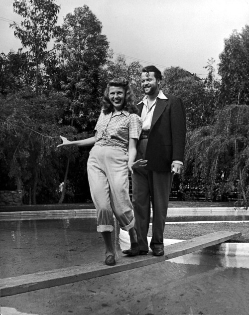 avasgal:  Rita Hayworth and Orson Welles walking on a wooden board that crossed over their pool. Rita's face is the cutest thing in the world!