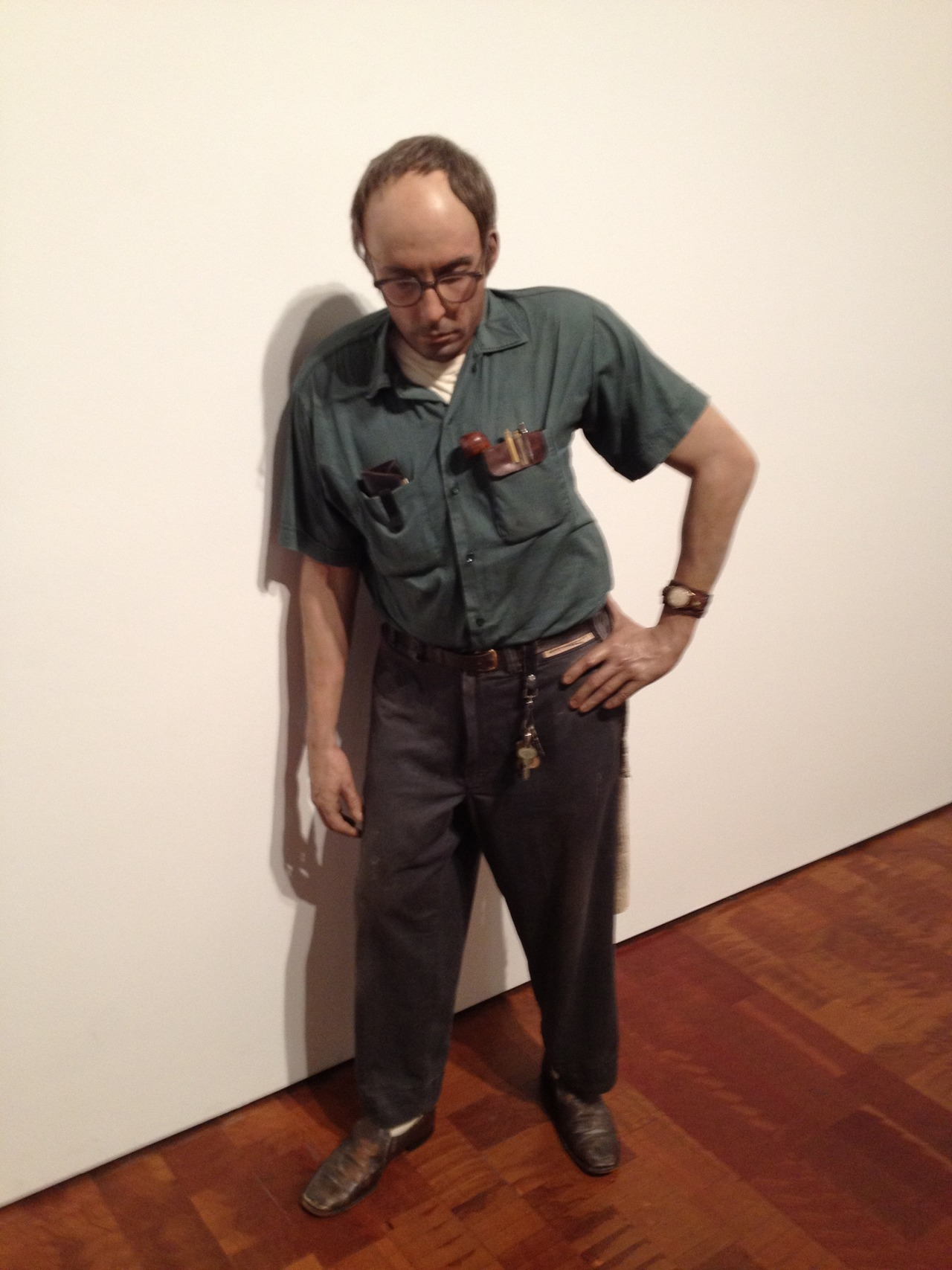 philolspice:  Duane Hanson (1925-1996) Janitor 1973 Polyester, fiberglass, and mixed media Duane Hanson is well known for his hyper-realistic figures made of polyester and cast fiberglass, enhanced by real clothing, accessories and props. The realism of his sculptures draws the viewer in for a closer look and links Hanson with the Photorealist painters who also explored methods of copying as a form of image making. Hanson's intent, however, was not merely to reproduce reality but also to comment on the human condition. His subjects are ordinary people leading unremarkable lives-a cleaning lady, a woman shopping, a man mowing his lawn. the artist's desire to infuse an emotional quality into his figures is evident in the janitor.  The humpbacked figure dressed in his work clothes leans against the nearest support and stares downward with one hand on his hip. His blank expression signifies resignation and the hopelessness of those caught in the daily grind.