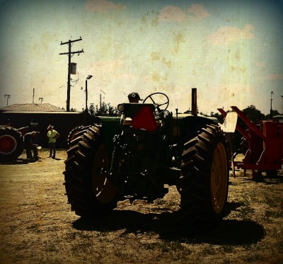 John Deere:) little dude playing on his grandpas antique tractor at the show; how adorable :)