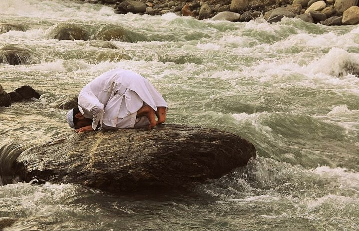 um-er:  A man offers prayer on a stone in the fast flowing river Swat.