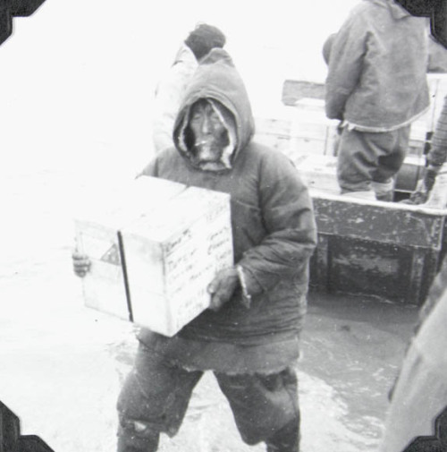 "Unidentified Inuit man unloading cargo from the M.V. Regina Polaris. ""Every eskimo is working around the clock when Polaris is in. bad weather is a common occurrence""   Place Unknown, N.W.T. [Nunavut], 1952 Credit: James Vinton Stowell / Library and Archives Canada / e004413798 Source"