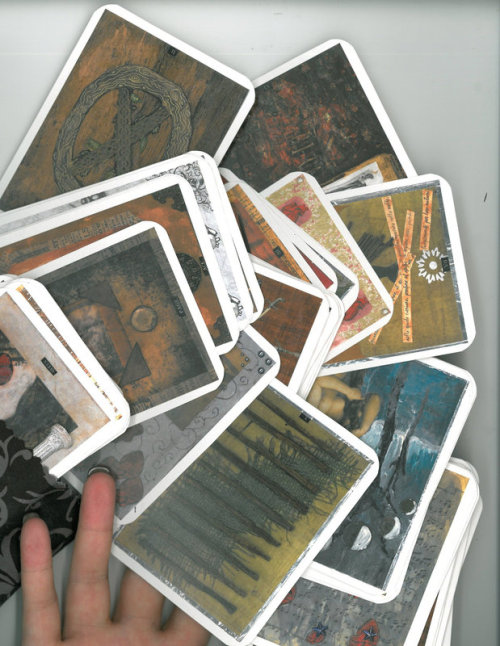 A scattering of cards with my hand for scale- I was pleasantly surprised how well they scaled down in size!