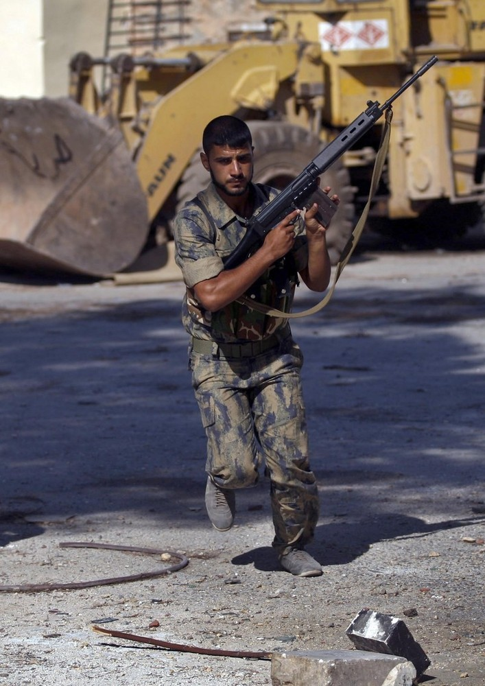 On this Sunday Aug. 5, 2012, a 'Free Syrian Army' fighter holds his FAL rifle as he runs for cover during a mortar attack in the town of Atareb on the outskirts of Aleppo, Syria.