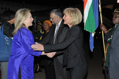 U.S. Secretary of State Hillary Rodham Clinton is greeted by Mrs. Liz Berry Gips, wife of U.S. Ambassador to South Africa Donald Gips, upon her arrival to Johannesburg, South Africa, on August 6, 2012. [State Department photo/ Public Domain]