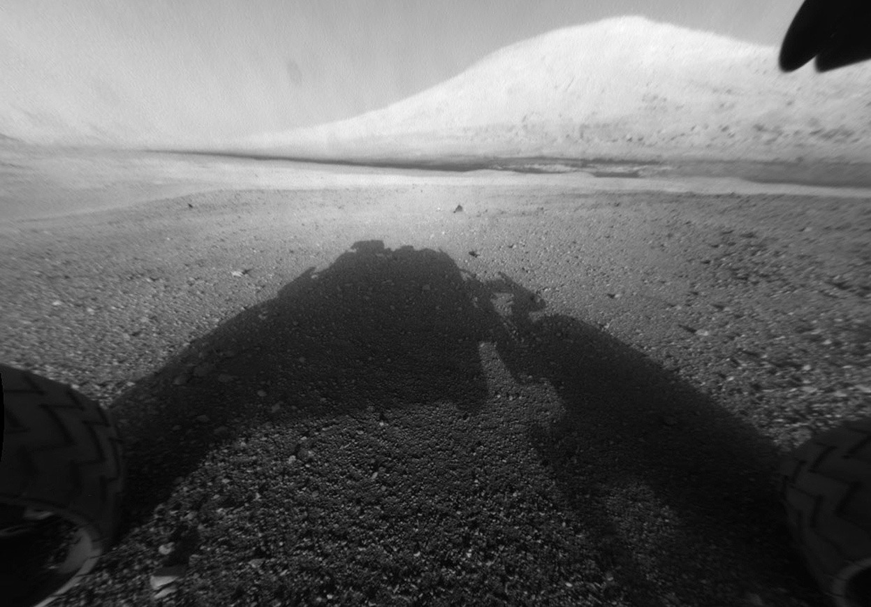 From Curiosity Lands on Mars, one of 31 photos. An image taken by NASA's Mars science rover Curiosity shows what lies ahead for the rover — its main science target, Mount Sharp, in this photo released by NASA on August 6, 2012. The rover's shadow can be seen in the foreground, and the dark bands beyond are dunes. Rising up in the distance is Mount Sharp at a height of about 3.4 miles, taller than Mt. Whitney in California. The Curiosity team hopes to drive the rover to the mountain to investigate its lower layers, which scientists think hold clues to past environmental change. The image has been linearized to remove the distorted appearance that results from its fisheye lens. (Reuters/NASA-JPL-Caltech)